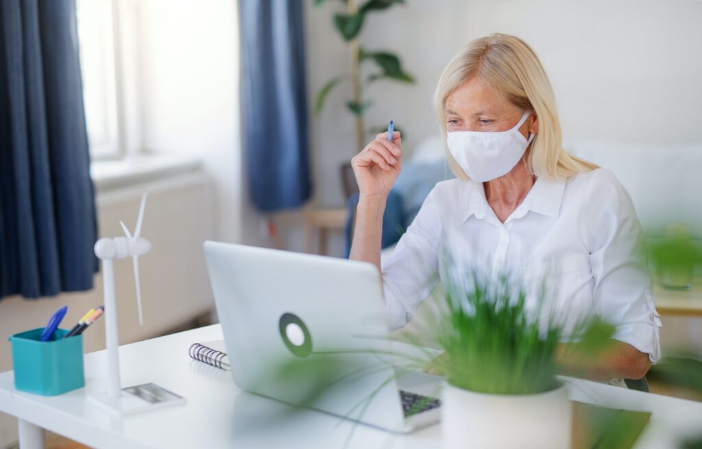 Senior woman engineer with face mask and laptop indoors in office, working
